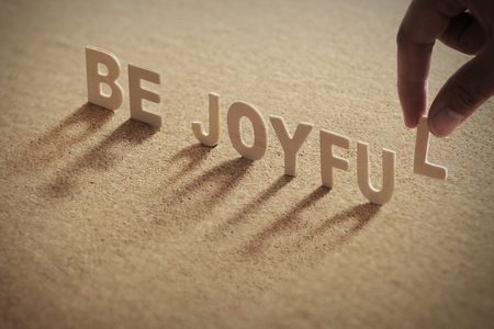 BE JOYFUL wood word on compressed or corkboard with human's finger at L letter.