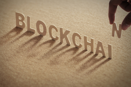 BLOCKCHAIN wood word on compressed or corkboard with human's finger at N letter.