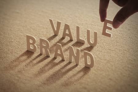 BRAND VALUE wood word on compressed or corkboard with humans finger at E letter.