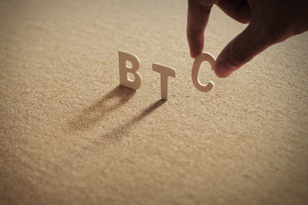 BTC wood word on compressed or corkboard with human's finger at C letter. Standard-Bild