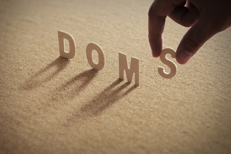 DOMS wood word on compressed or corkboard with human's finger at S letter.