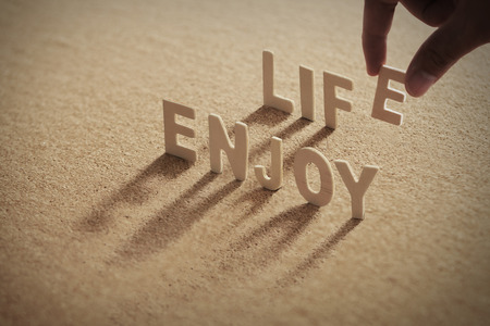 ENJOY LIFE wood word on compressed or corkboard with human's finger at E letter.