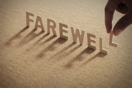FAREWELL wood word on compressed or corkboard with human's finger at L letter. Standard-Bild