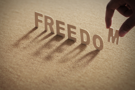 FREEDOM wood word on compressed or corkboard with human's finger at M letter.