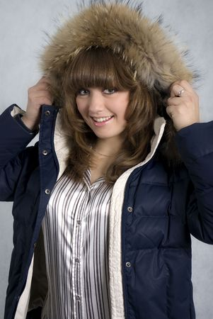 fur hood: A smiling girl in a winter jacket with a hood edged by fur