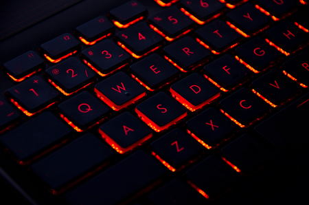 Close up. Red backlight on laptop or keyboard computer of gaming in the dark