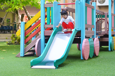 Asian little girl playing slider at playground bangkok thailand Stock Photo