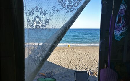 The view through the door of a motorhome parked on the beach at Puntas de Calnegre in Spain