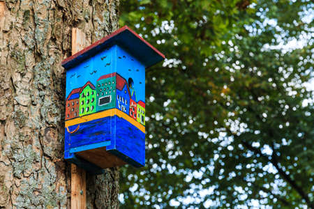 dutch canal house: Colorful birdhouse showing canal houses in Amsterdam. Side view showing leafs tree in unsharp background.