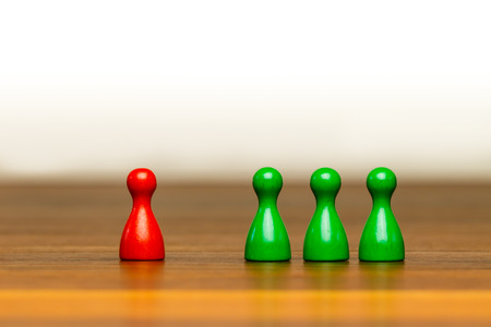 acceptable: Concept for: good or bad, isolation, confrontation, competition and difference. With colorful red and green pawn figures on wooden surface and white background.