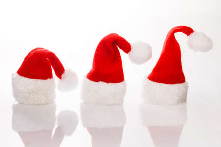 Three hats Santa in a row for Christmas. Isolated on white background with reflection. Room for text, copy space. photo