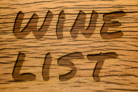 carved letters: Wine list text carved into wood. Message on old oak wood background. Shadow inside letters.
