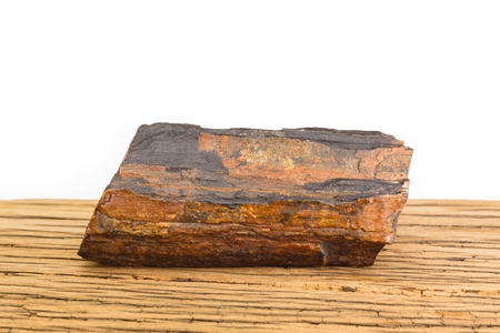 earthing: Brown piece of petrified wood on old oak surface, white background. Ancient natural gem stone.