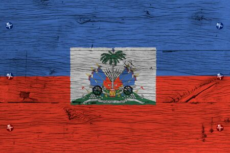 port au prince: Haiti national flag with coat of arms. Painting is colorful on wood of old train carriage. Fastened by screws or bolts. Stock Photo
