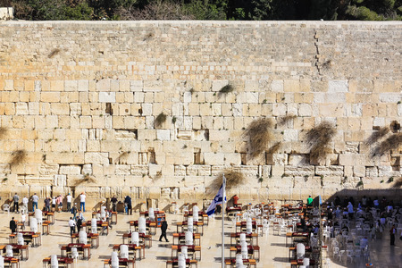 Western wall in Jerusalem, Israel. Prayers at the wailing wall in the old city, shadow moving over square.