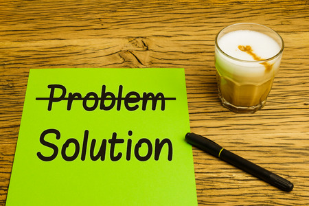 strikethrough: Business concept problem to solution with green page strikethrough text. Marker and coffee on oak desk. Stock Photo