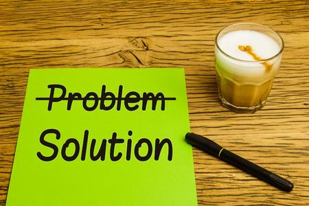 tachado: Problema de concepto de negocio de la soluci�n con el texto tachado p�gina verde. Marker y caf� en la mesa de roble. Foto de archivo