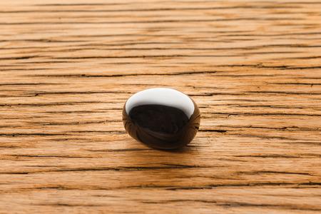 igneous: Obsidian on oak wood surface. Igneous gem stone high glossy.