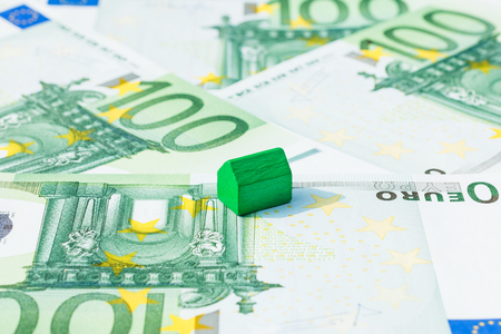 subprime mortgage crisis: Concept house sell, pay bill, mortgage on 100 euro banknotes. Focus on green house. Stock Photo