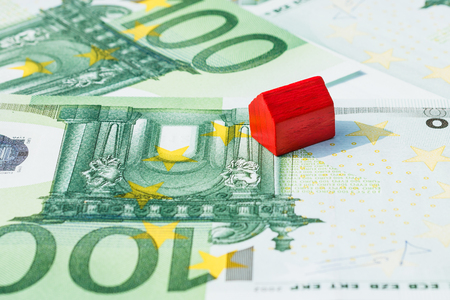 subprime mortgage crisis: Concept house sell, foreclosure, debt, bill, mortgage on 100 euro banknotes. Focus on red house.