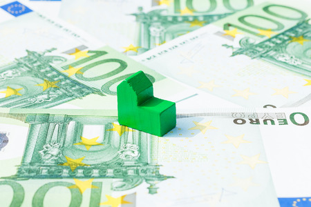 subprime mortgage crisis: Concept house, bill, income, salary, mortgage on hundred euro banknotes. Focus on green house.