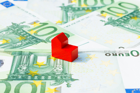 hard sell: Concept church sell, loan, debt, bill on hundred euro banknotes. Focus on red church.