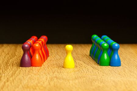 Concept for: team, leader, leadership, adoration. With colorful pawn figures on oak wood surface. Stock Photo