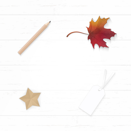 Flat lay top view elegant white Christmas composition paper, autumn maple leaf, pencil, tag and star shape craft on wooden background.