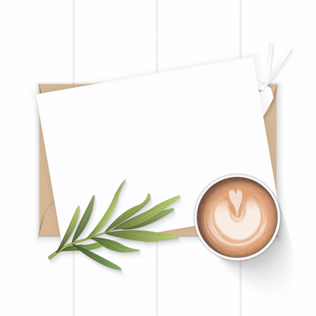 Flat lay top view elegant white composition paper, kraft envelope, tarragon leaf tag and coffee on wooden background.