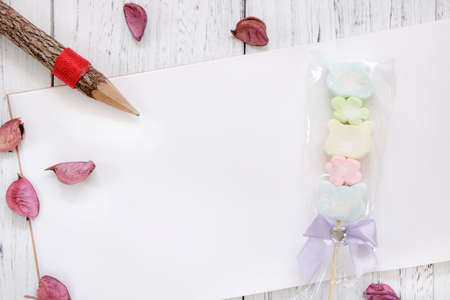 Stock Photography flat lay vintage white painted wood table note book paper flower petals cotton candy pencil