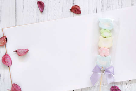 Stock Photography flat lay vintage white painted wood table note book paper flower petals cotton candy