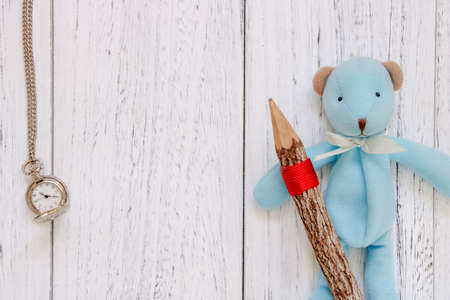 Stock Photography flat lay vintage white painted wood table blue bear doll holding pencil pocket clock
