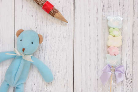 Stock Photography flat lay vintage white painted wood table blue bear doll cotton candy pencil 写真素材