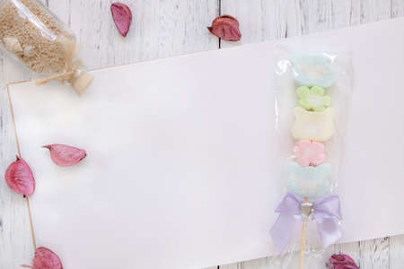 Stock Photography flat lay vintage white painted wood table note book paper flower petals cotton candy glass sand bottle