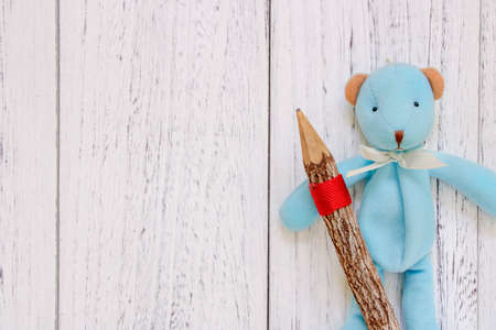 Stock Photography flat lay vintage white painted wood table blue bear doll holding pencil 写真素材