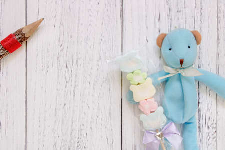 Stock Photography flat lay vintage white painted wood table blue bear doll holding cotton candy pencil