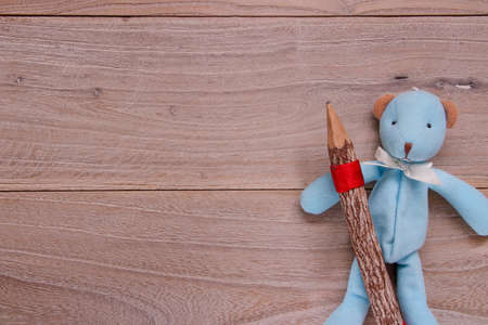 Stock photography flat lay template blue bear doll holding wooden pencil on plank table 写真素材