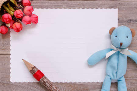 Stock photography flat lay template wooden plank table white letter paper blue bear doll pencil rose flower
