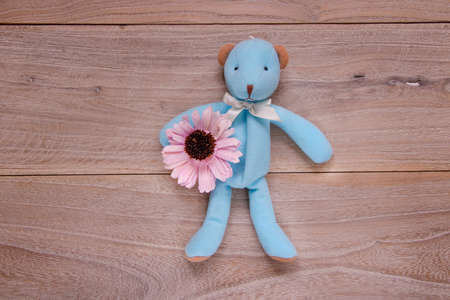 Stock photography flat lay plank table template blue bear doll holding purple cute flower 写真素材