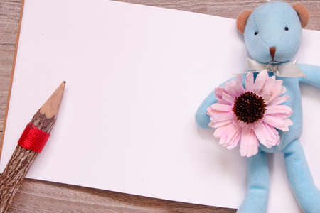 Stock photography flat lay template wooden pencil blank sketch white paper blue bear doll purple flower