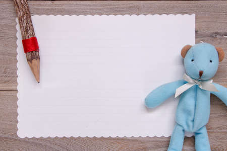 Stock photography flat lay template wooden plank table white letter paper blue bear doll pencil