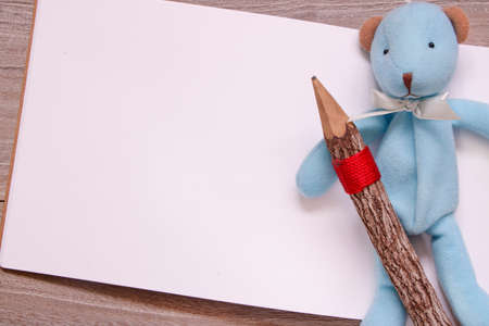 Stock photography flat lay template wooden pencil blank sketch white paper blue bear doll