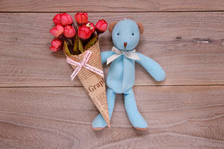 Stock photography flat lay plank table template blue bear doll holding rose flower