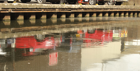 water s: A Row of parked cars on the water s edge reflected
