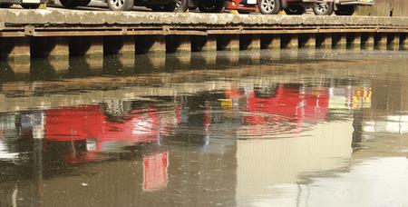 water s edge: Fila di macchine parcheggiate sul bordo dell'acqua s riflessa Archivio Fotografico