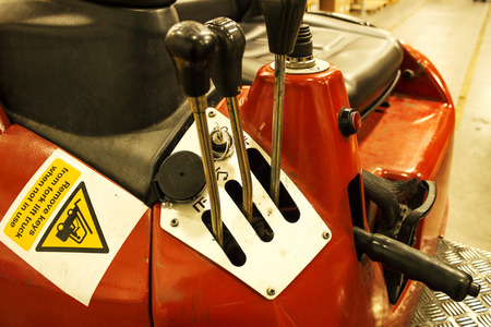 run down: Worn and run down red forklift control levers and seating