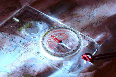 Orienteering compass resting on a map illuminated by torchlight.