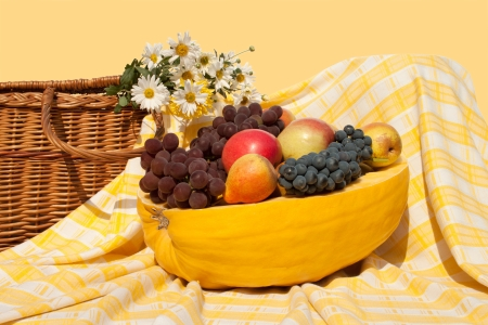 The still life from fruits, put in the pumpkin, with a pad and flowers, draped with squared tablecloth photo