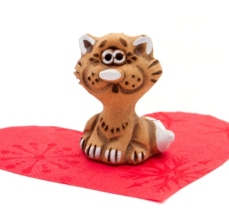 The figurine of charming kitty seating on the heart-shaped napkin photo