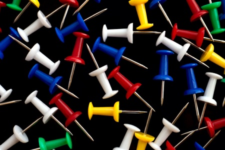 sheeted: The heap of variegated push pins on the black background Stock Photo